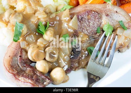 An English meal of Barnsley chop and Mushroom reduction served with Creamed Potato, glazed Carrot and Savoy cabbage. - Stock Image