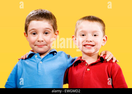 Stock photo of two children over yellow background - Stock Image
