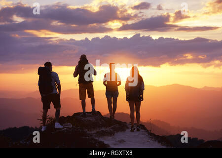 Group of four tourists or friends stands on mountain top and looks at sunset. Peoples travel concept - Stock Image