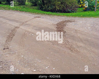 Braking traces after traffic accident on curved gravel road surface - Stock Image