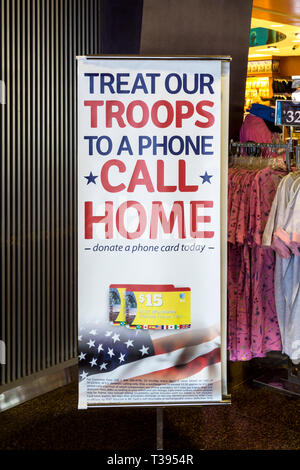A sign at Seattle airport invites people to Treat Our Troops to a Phone Call Home, by donating a phone card. - Stock Image