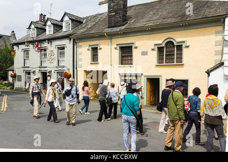 A group of tourists explore the village of Hawkshead in Cumbria. The village is a popular tourism destination for - Stock Image