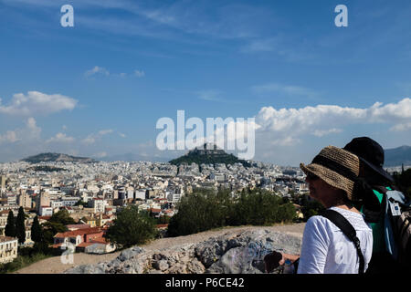 Couple on the Acropolis, enjoying the views of Athens and Mount Lycabettus ( Lycabettos ), and the blue skies, Athens, Greece. - Stock Image