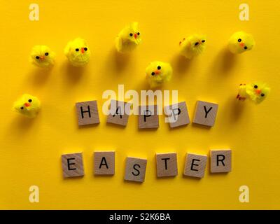 Happy Easter message with fluffy chicks on bright yellow background - Stock Image