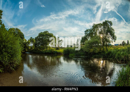 Reflection of trees and sky in the water. - Stock Image