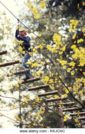 boy crossing high ropes - Stock Image