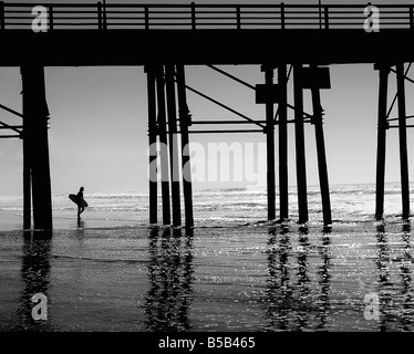 USA A surfer gets ready to hit the waves dreaming of an endless summer in Southern California enhanced image - Stock Image