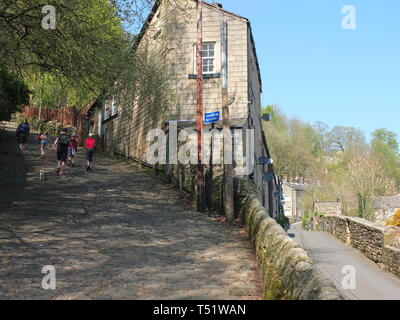 Walkers begin their ascent of 'The Buttress', Hebden Bridge - a steep cobbled footpath leading from the Calderdale town to the village of Heptonstall - Stock Image