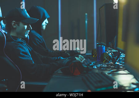 Group of concentrated hackers in black hoodies sitting in line at table and breaking into classified data - Stock Image