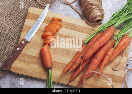 Still life of carrots sliced knife and cutting board on the table top view - Stock Image