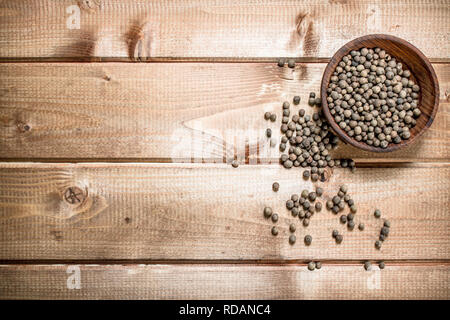 Black pepper in the bowl. On a wooden background. - Stock Image