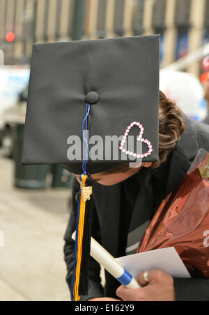 Manhattan, New York, U.S. - May 21, 2014 - On 7th Avenue, a young man who graduated from Pace University that day tilts his head to show the top of his black graduation mortar board hat, which is decorated with a rhinestone pink heart, in Manhattan. A blue and gold tassel topper is handing from the hat. - Stock Image