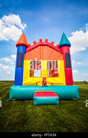 Inflatable bounce castle house in a large open yard. - Stock Image