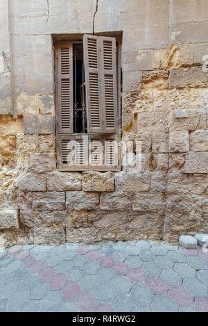 Broken windows and grunge stone bricks wall in abandoned Darb El Labana district, Cairo, Egypt - Stock Image
