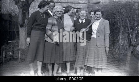 1930s, historical,  group of ladies standing together outside in a garden having a laugh and a cigarette, England, UK. - Stock Image