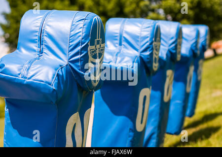 Football practice tackling and blocking dummies on a training sled. - Stock Image