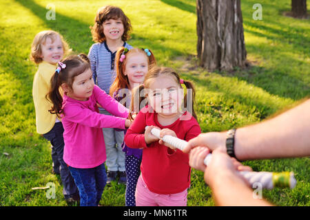 a group of small preschool children play a tug of war in the park.  - Stock Image
