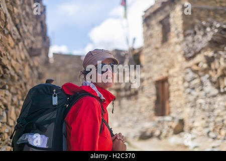 Portrait Young Pretty Woman Wearing Red Jacket Backpack Crossing Mountains Village.Mountain Trekking Rocks Path.Old - Stock Image