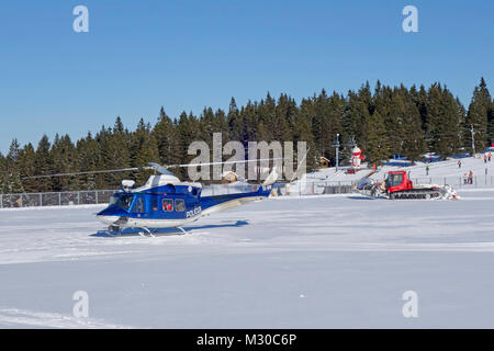 Police helicopter on intervention at Rogla ski resort, Pohorje, Slovenia. - Stock Image