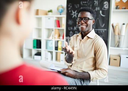 Successful young teacher pointing at schoolgirl while asking her question during explanation of subject - Stock Image