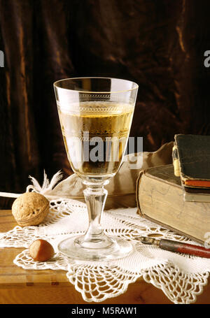 Vintage still life with glass of white wine, nuts, book,  pen and feather - Stock Image