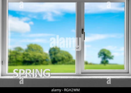 Decor spring in a window sill with a view to a green garden under a blue sky in the springtime - Stock Image
