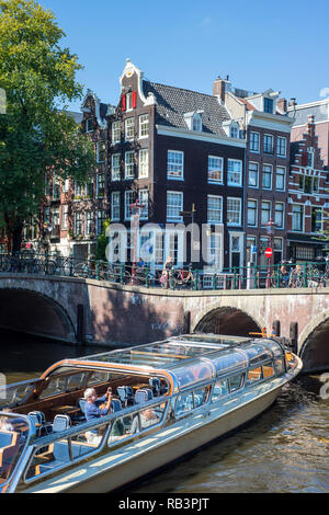Tourist boat on the canals in Amsterdam, the Netherlands - Stock Image