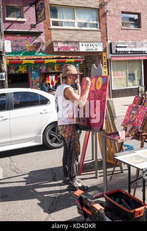 Street Artist Steel Daniels paints on a painting on Augusta St in Kensington Market in downtown Toronto Ontario - Stock Image