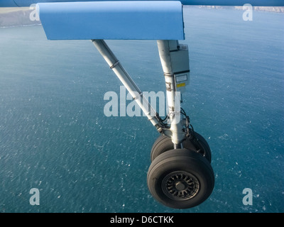 Landing gear of plane on its approach to landing,over the sea.It is a Flybe plane landing in the Isle of Man.Sunny, - Stock Image