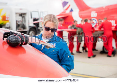 Woman by ear muffs on Red Arrows airplane on RAF Scrampton, UK - Stock Image