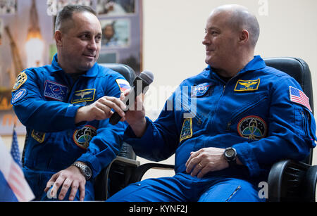 Expedition 54 Soyuz Commander Anton Shkaplerov of Roscosmos, left, passes a microphone to flight engineer Scott - Stock Image