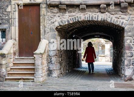Senior woman wearing red coat walking through arched narrow passage, Bakehouse Close, Royal Mile, Edinburgh, Scotland, UK - Stock Image