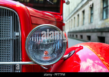 Headlamp of vintage red car on a background of the old town - Stock Image