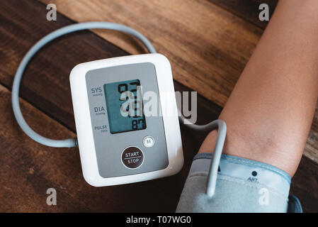 man checking his blood pressure using electronic blood pressure monitor or sphygmomanometer on a wooden table. concept of healthcare, medical instrume - Stock Image