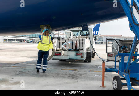 Female lav agent. Girl station attendant emptying a lavatory system of plane airplane aeroplane on tarmac. Woman - Stock Image