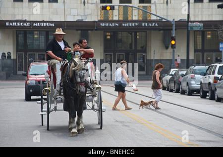 Family riding on horse cart downtown in Galveston, Texas, USA - Stock Image