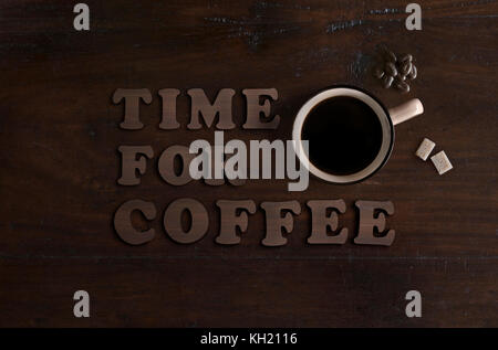 flat lay of cup of organic coffee, biological cane sugar cubes and fair trade chocolate beans, on dark wooden background - Stock Image