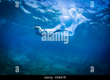 Young female swimmer in the sea with a long flowing white wrap - Stock Image