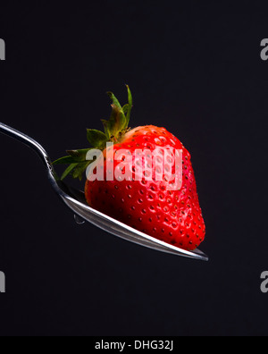 A Silver Spoon Sulverware Utensil Holds Fresh Raw Food Red Strawberry Sweet Snack - Stock Image