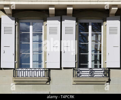Details of old medieval style building. The building has beige concrete walls and the window frames are white and made of wood. Photographed in Nyon. - Stock Image