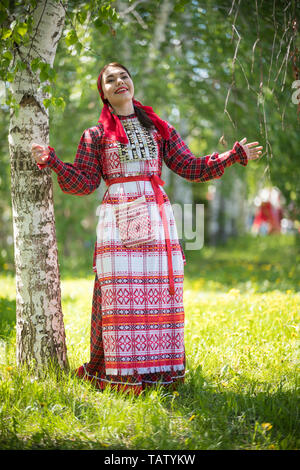 Young woman in traditional russian clothes standing in the forest and throws up her hands - vertical shot - Stock Image