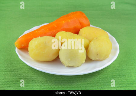 Peeled boiled vegetables on a white plate - Stock Image
