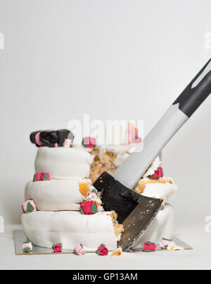 Wedding cake cut with axe - Stock Image