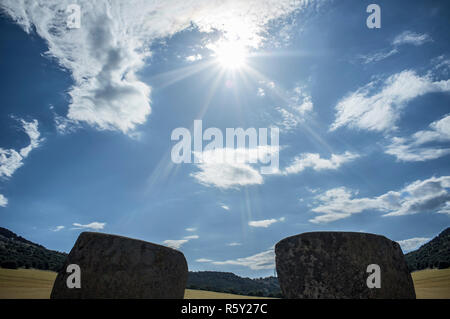 Sun descending between entry orthostates of Magacela Dolmen, Extremadura. Spain. Perfect east orientation - Stock Image