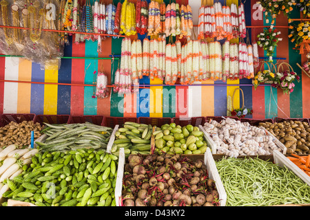 Produce and flower garlands sold at an open market in Little India, Singapore - Stock Image