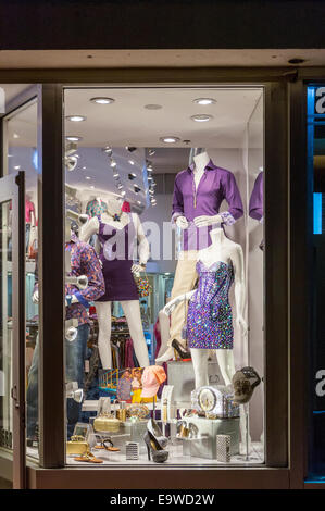 Purple dresses and clothing on mannequins on display with accessories in a small retail shop window in Miami Beach, - Stock Image
