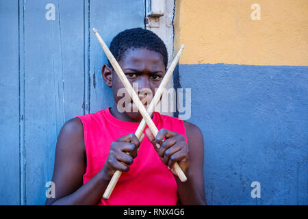 Portrait of young African-American street drummer boy looking at camera holding drumsticks on Bourboun Street, New Orleans French Quarter New Orleans - Stock Image
