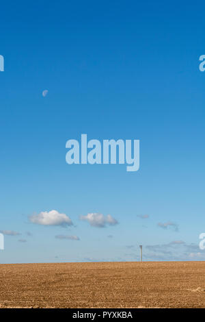 Prepared field (after ploughing) with blue autumnal sky behind - with moon. - Stock Image