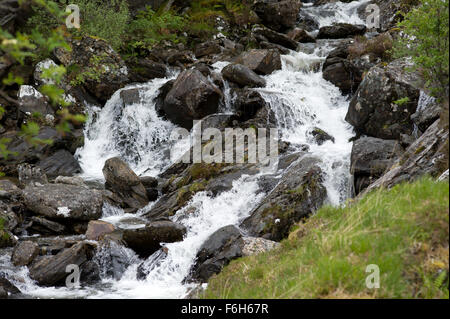 Allt Coire Giubhsachan tumbles over rocks from the Nevis Range and eventually into the Water of Nevis in Glen Nevis - Stock Image