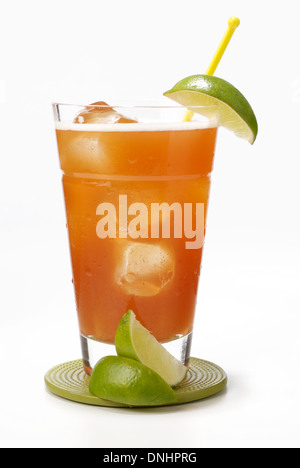 A orange cocktail drink in a glass with a green lime wedges as garnish. - Stock Image